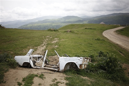 A view on the remains of body shell of Lada car near the road in the mountains of Dagestan.